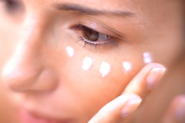 Woman applying moisturiser on face