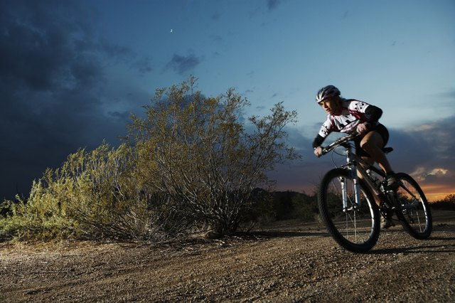 Female rider mountain biking on dirt track at dusk