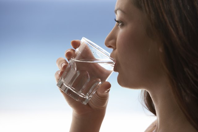 Young Woman Drinking Water by Sea