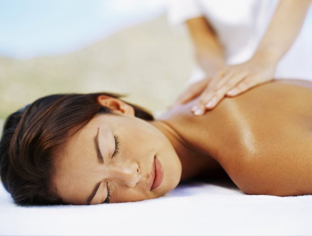 close-up of a young woman getting a back massage from a massage therapist