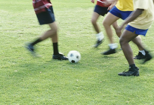 People playing football outdoors,low section