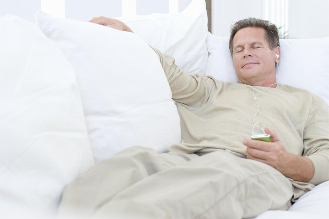 Middle-aged man listening to music on sofa