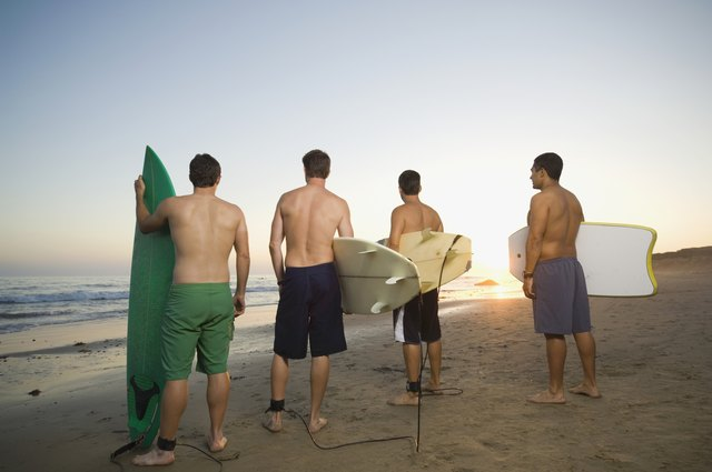 Rear view of multi-ethnic surfers