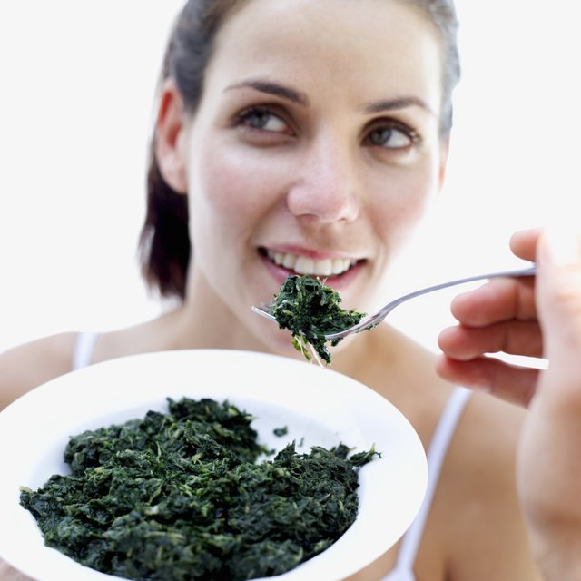 close-up of a woman being fed spinach