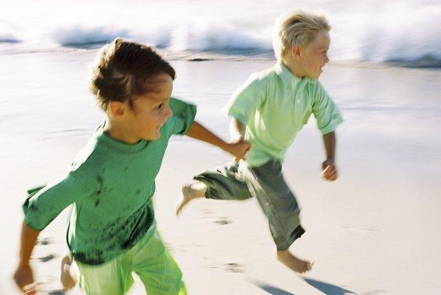 Boys running barefoot on beach