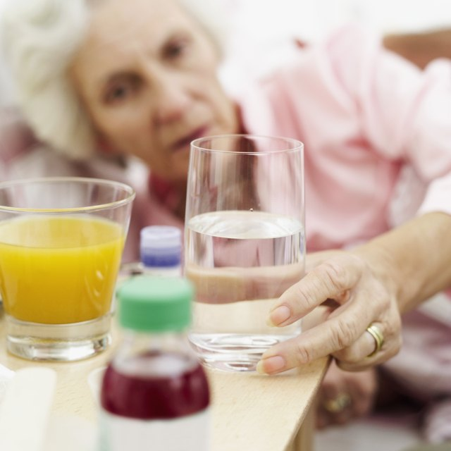 senior woman reaching out for a glass of water