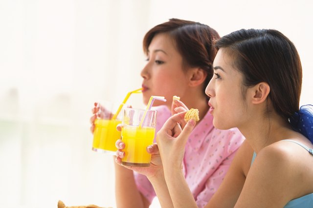 Two women holding glass of juice and eating