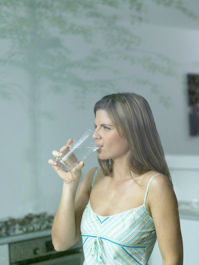 Woman drinking glass of water, view through window, close-up