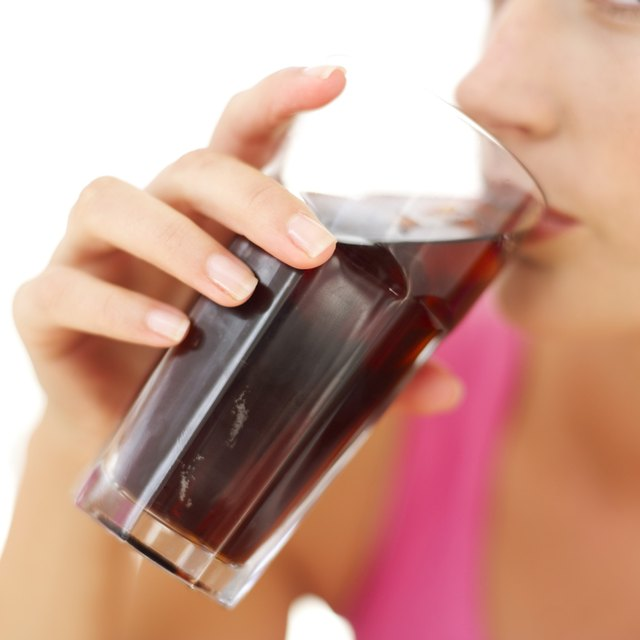 close-up of a woman drinking cola from a glass