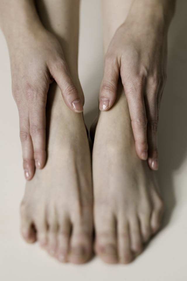 Woman holding hands on feet, close up of feet,, close-up