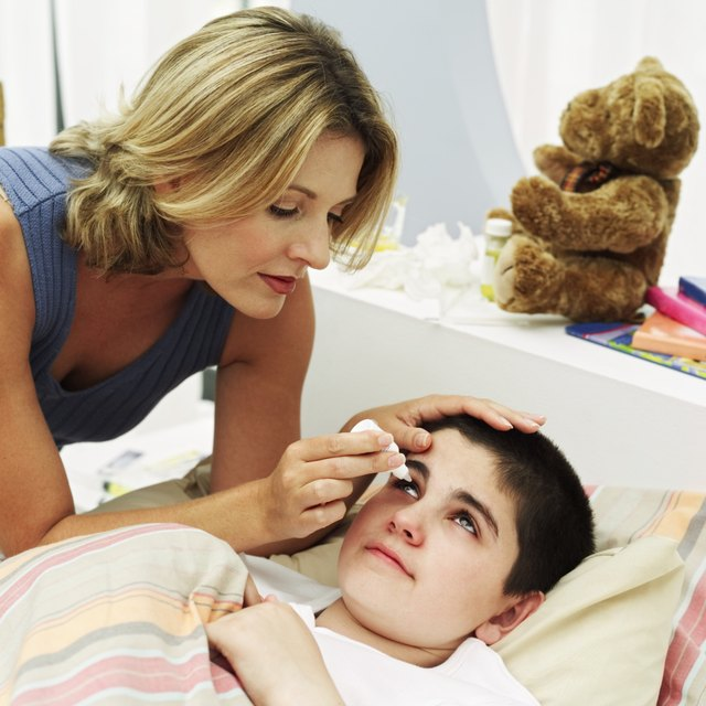 Side view of a woman dropping eye drops in the eye of a boy (10-12) lying in bed