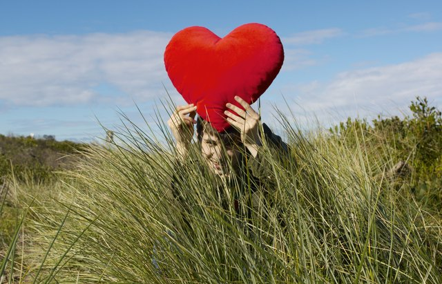 Young man squatting in grass holding up heart-shaped cushion