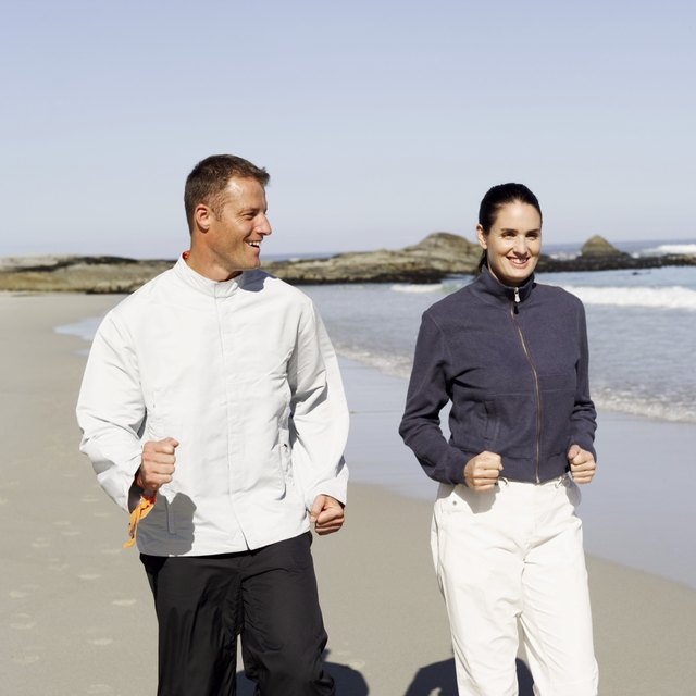 couple power walking on the beach