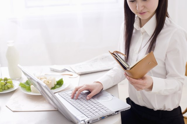 Young woman using laptop at dining table, looking at personal organizer