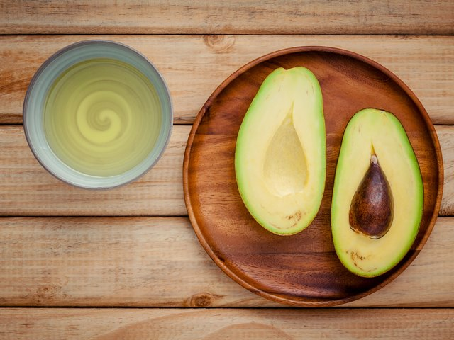 Fresh avocado and oil on wooden background. Organic avocado heal