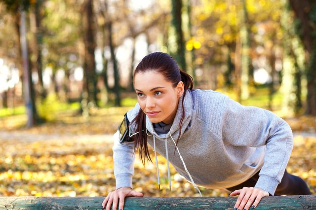 Sporty woman doing push-ups in the park