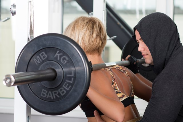 Woman lifting bar bells with her personal trainer
