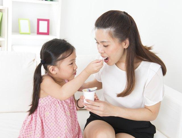 Beautiful child feeding mother yogurt