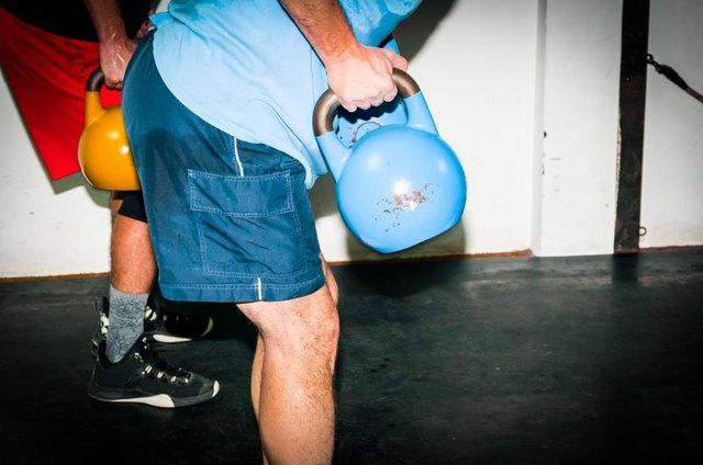 Intensive fitness training. Side view of young man in sportswear working out with kettle bell at gym. Selective focus, real time workout, no posing.