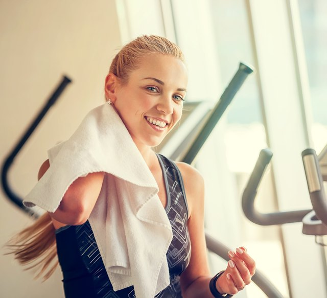 Attractive female with towel after Treadmill exercise
