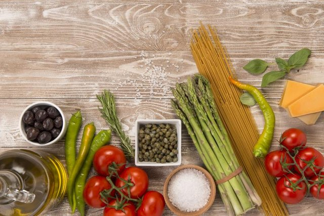 Fresh vegetables, parmesan cheese, olive oil, pasta and olives on wood surface