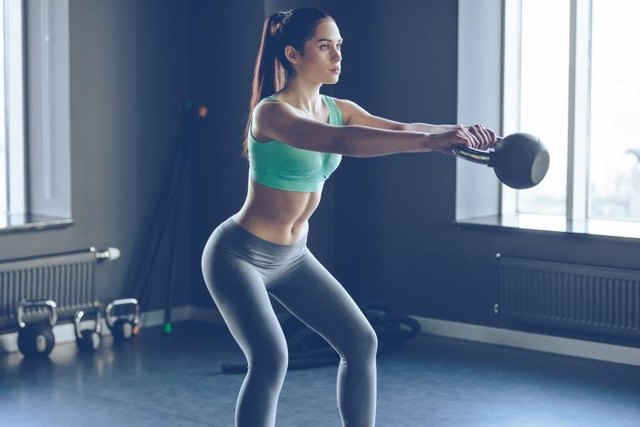 Side view of young beautiful woman with perfect body in sportswear working out with kettle bell at gym