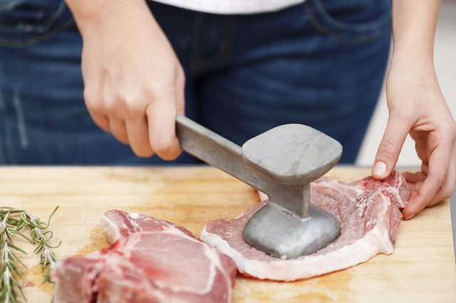 Young woman beating a steak