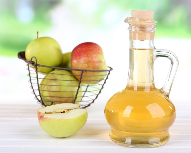 Apple cider vinegar in bottle and apples, on table