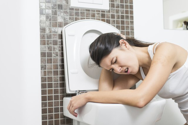 Woman vomiting into the toilet bowl