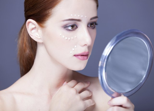women with cosmetic cream on a chee