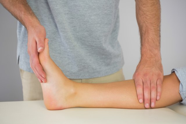 Physiotherapist checking patients foot