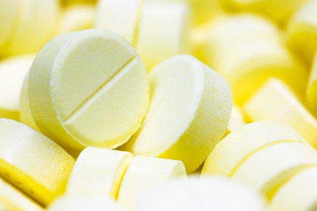 Heap of yellow round medicine tablet antibiotic pills. Shallow DOF