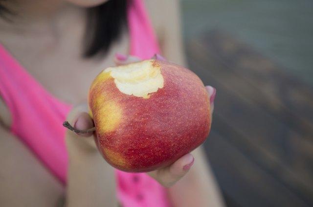Beautiful girl eating fresh apple