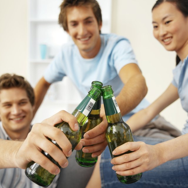 Close-up of three young people sitting on sofa and toasting with bottles of beer
