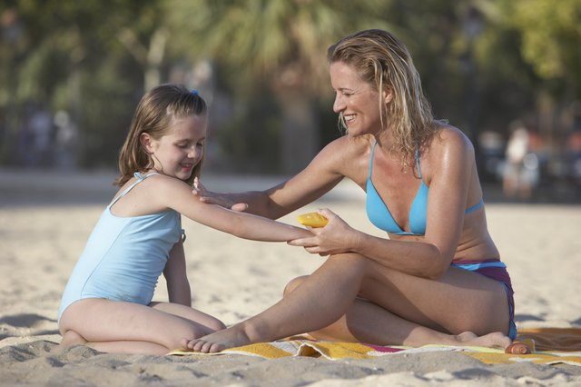 Mother putting sunscreen on daughter (7-9) on beach