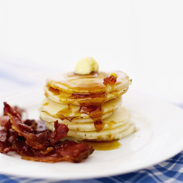 pile of pancakes served with butter and bacon rashers