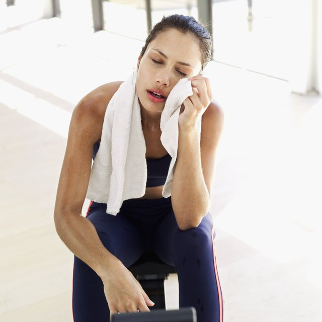 Young woman sitting on a rowing machine wiping her face after a workout