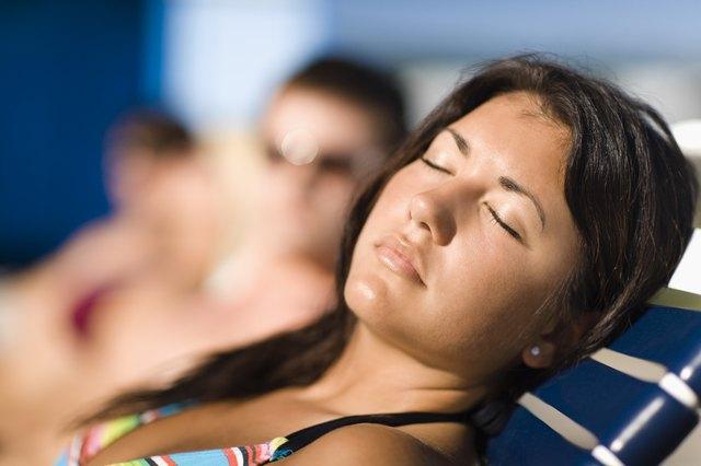 Woman sunbathing by swimming pool