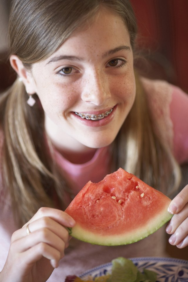 Portrait of a teenage girl holding a slice of watermelon