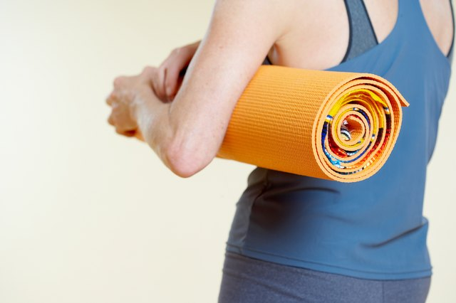 Woman with rolled yoga mat