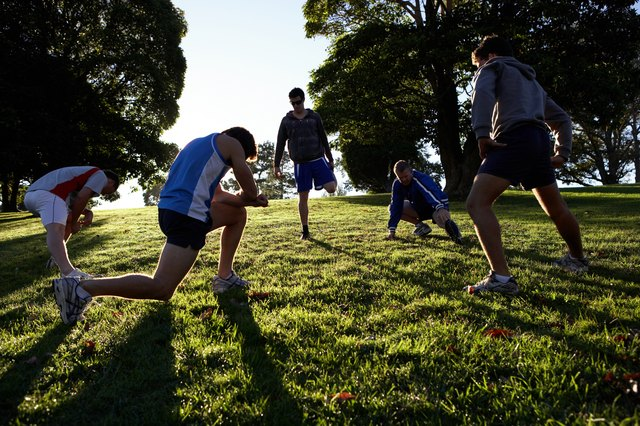 Five people stretching in park