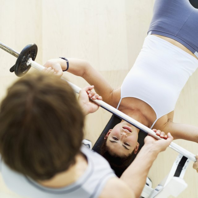 high angle view of a male instructor helping a young woman exercise with weights