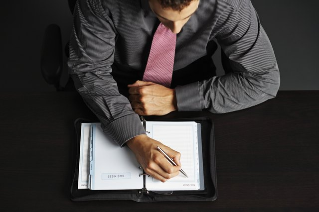 Businessman Writing in Daily Organizer