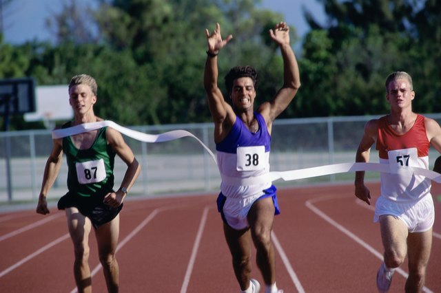 Portrait of male runners crossing the finishing line in a race