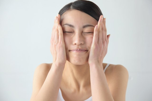 Woman putting on moisturizer