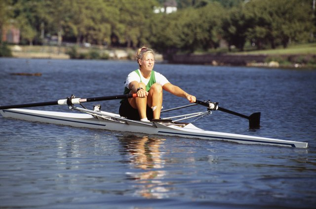 Young woman rowing scull on water