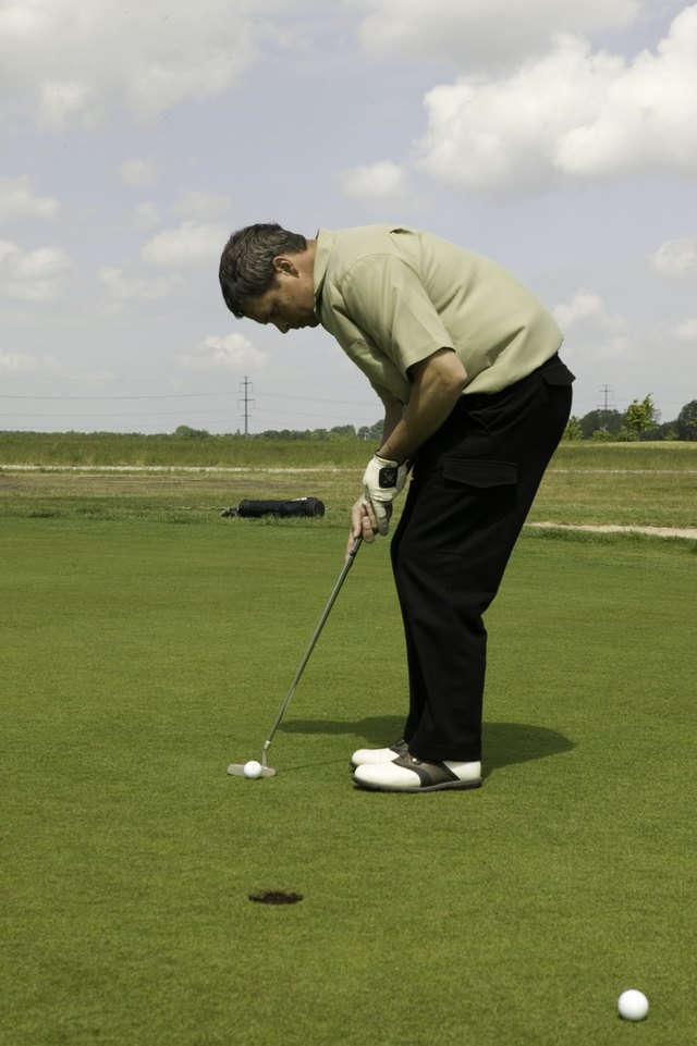 Man putting ball on golf course
