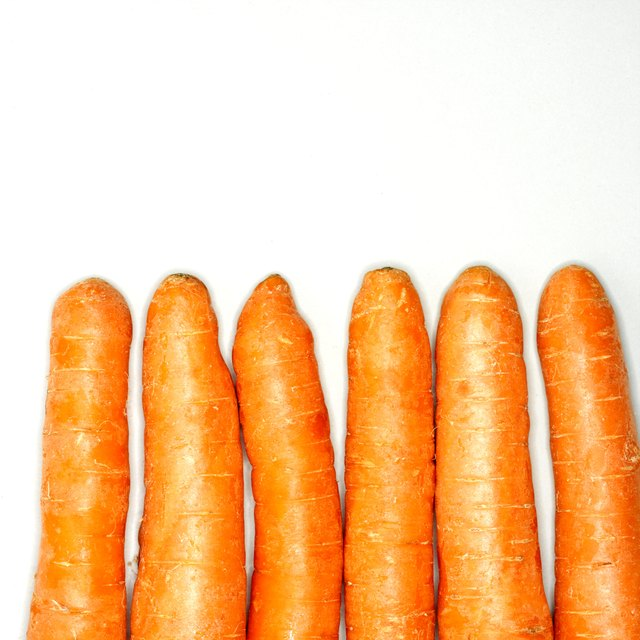 Six raw carrots in row, close-up