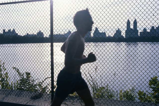 Bare-chested man running outdoors, side view