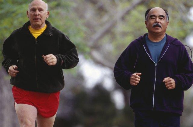 Two senior men jogging in park